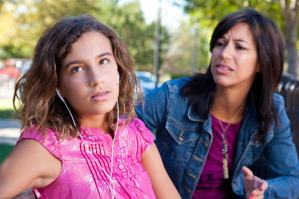 preteen daughter listening to music and rolling eyes with her mother trying to talk to her