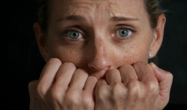 close up picture of anxious woman holding clenched hands to her mouth with black backdrop