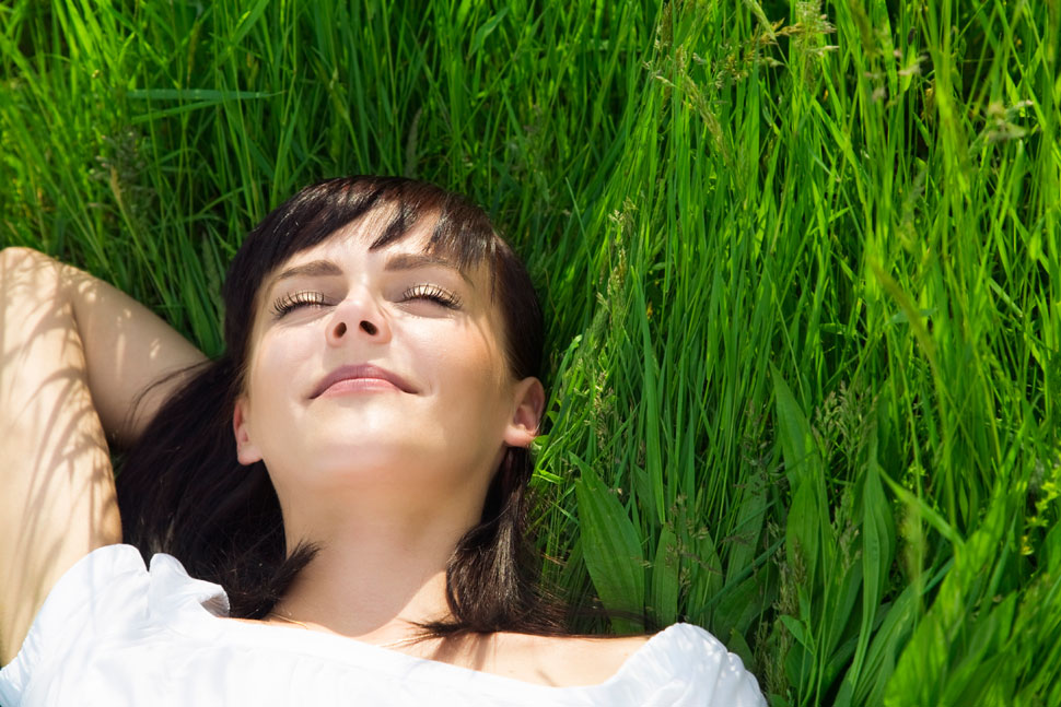 woman smiling with eyes closed, laying in green grass