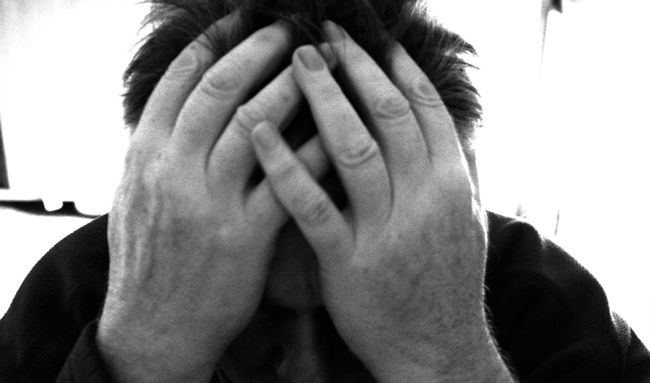 black and white picture of a man holding his head in his hands, feeling distraught