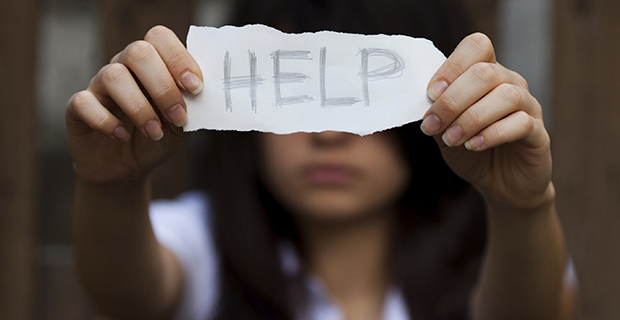 "young girl holding up piece of paper that reads ""Help"" in front of her face."