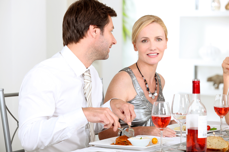middle aged couple sitting at table eating a meal with wine