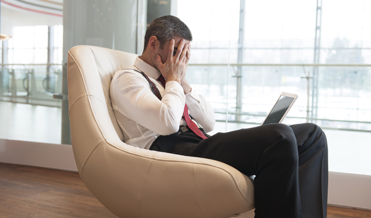 Anxious business man sitting in a chair, laptop in his lap, hands covering his face