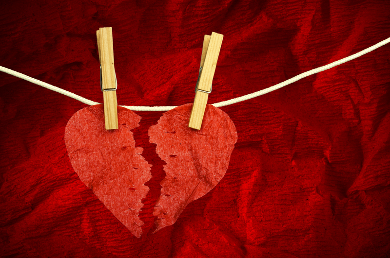 A paper heart ripped in two pieces, hanging from a line by clothes pins.