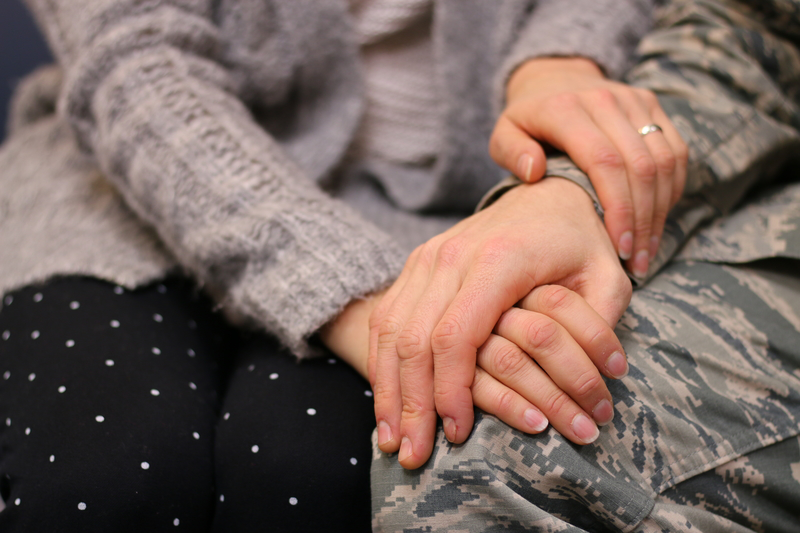 Military husband and wife holding hands