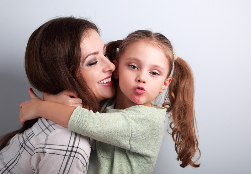 Young little girl hugging her mother while looking at camera.