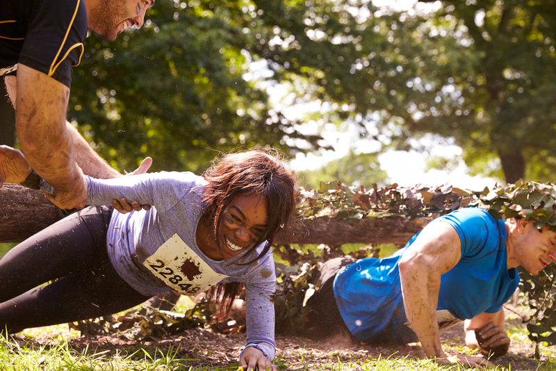 A man helping a woman through an obstacle during a team building exercise.