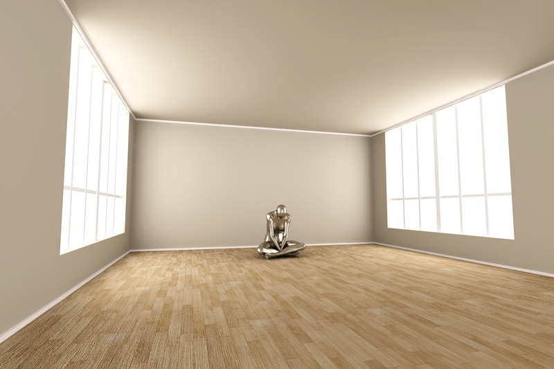 A silver figurine in a sitting position, alone in a room with wood floors and large windows.