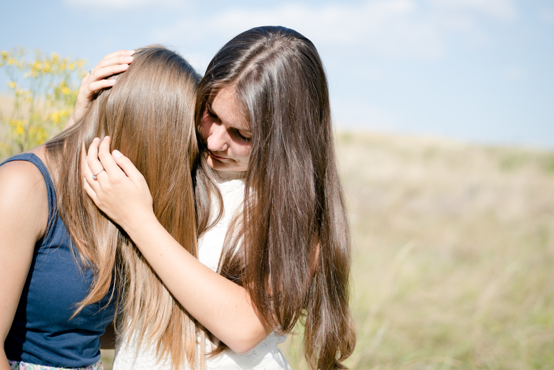 Two teenage girls consoling each other during a difficult time.