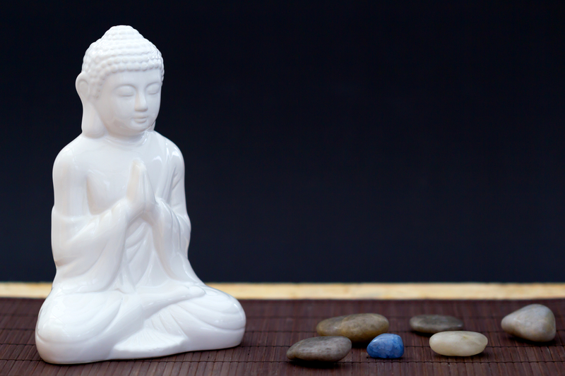 Peaceful picture of a small, white Buddha figurine with pretty rocks laying on ground.