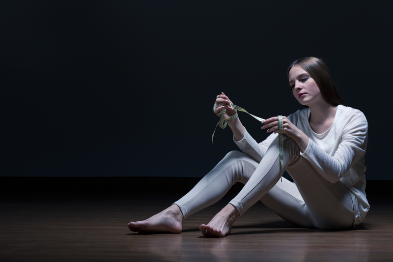 Young woman sitting in a dark room, wearing a one-piece jumpsuit, obsessing over her weight with a measuring tape in hand.