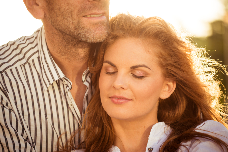 Happy middle-aged woman closing her eyes in happiness while her male partner embraces her.