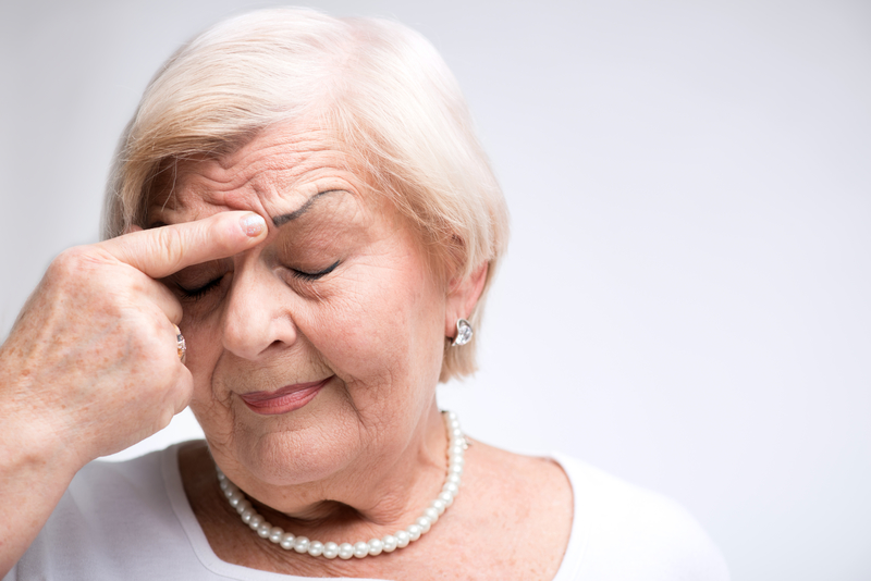 Elderly woman putting her finger on her head in dismay