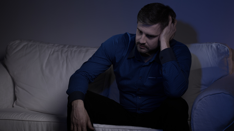 Man in dress shirt sitting on a couch in a dark room, dealing with trauma or depression