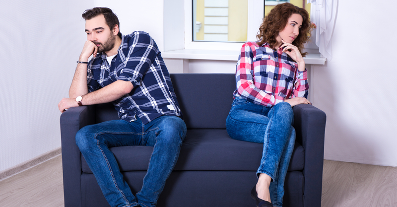 Unhappy 20-something couple sitting on a small couch together.
