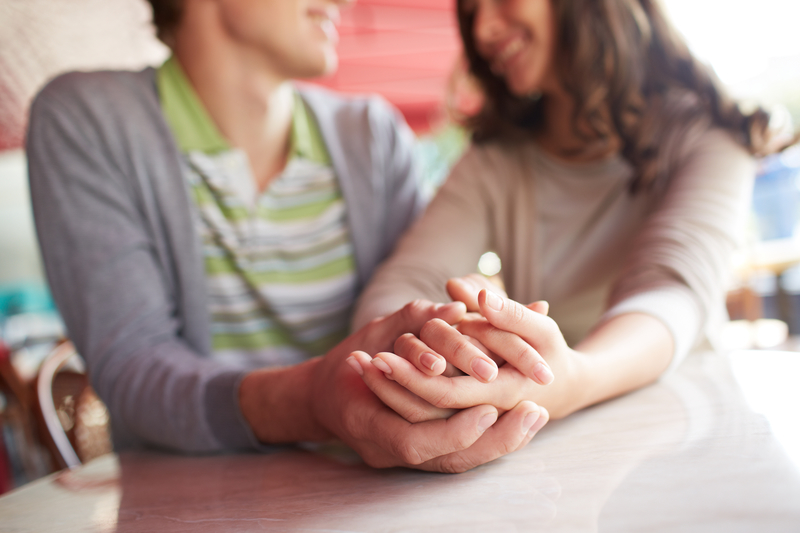 A male and female interlocking hands in what appears to be a strong, happy relationship.