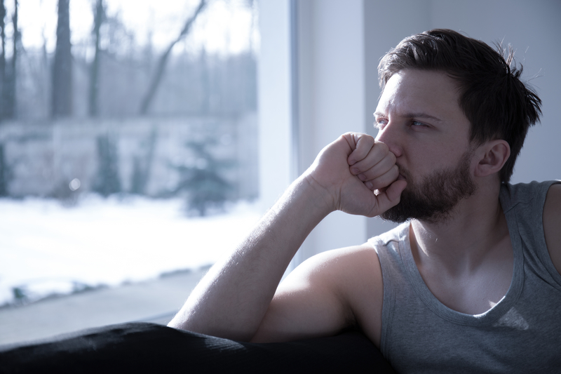 A man in his 20's who seems tired and anxious as he sits on a couch, looking out a window.