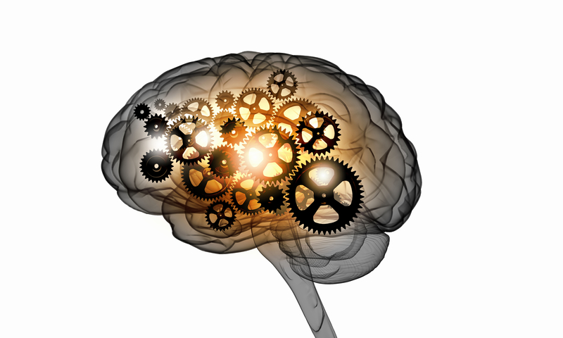 Picture of a brain lit up with machine pieces inside of it.