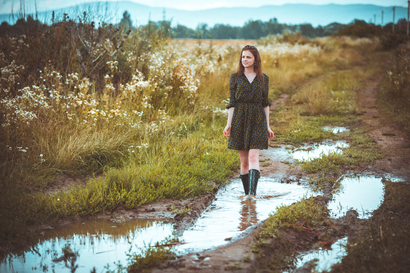 Girl with dress and rain boots on walking through rain puddles.